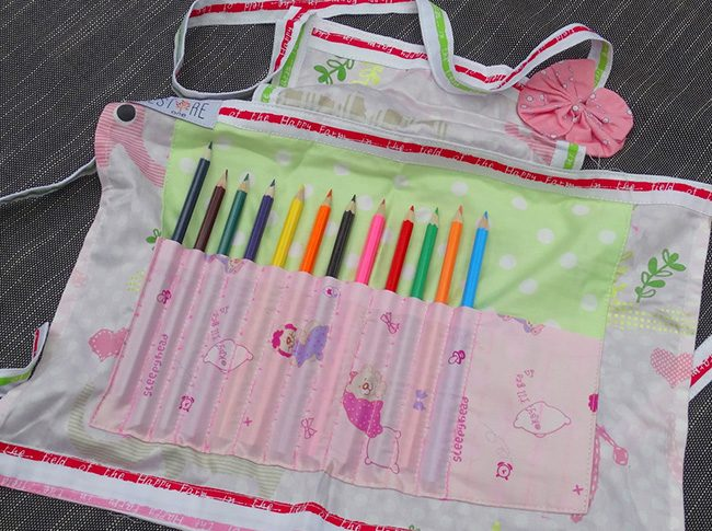 Childs apron with pencils in green and pink