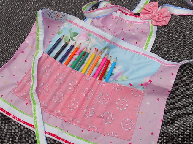 Childs apron with pencils in pink and blue
